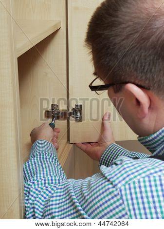 Carpenter fitting wardrobe hinge doors in walk-in closet