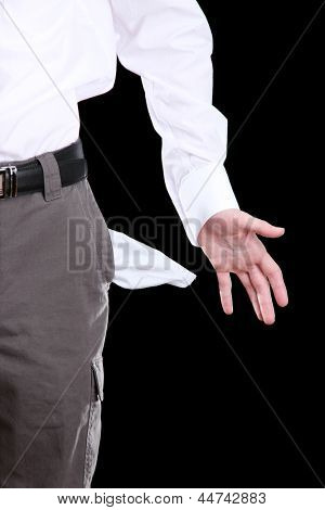 Business man showing his empty pocket, on black background