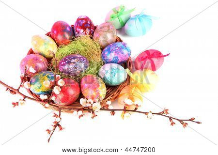 Beautiful Easter eggs in wicker basket on light background
