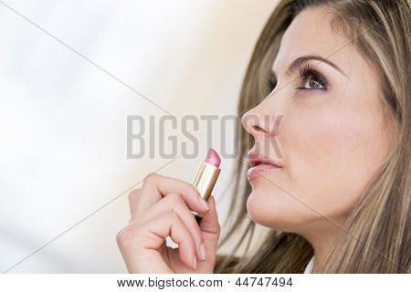 Portrait of a beautiful woman applying lipstick on her lips