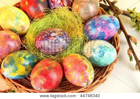 Beautiful Easter eggs in wicker basket on light background