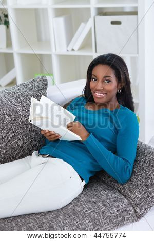 black woman reading book in living room
