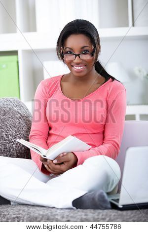 Smiling student woman sitting at sofa and reading book
