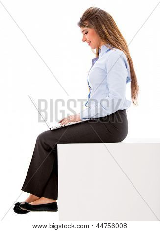Business woman sitting with a laptop - isolated over white background