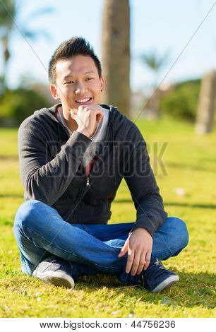 Portrait Of Young Asian Man Sitting In Park