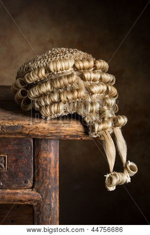 Antique court wig made of horsehair lying on an old desk