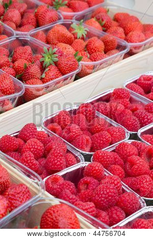 Fresh raspberries and strawberries on display at a greengrocery shop