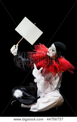 Young Pierrot sitting on a black background holding an empty sign