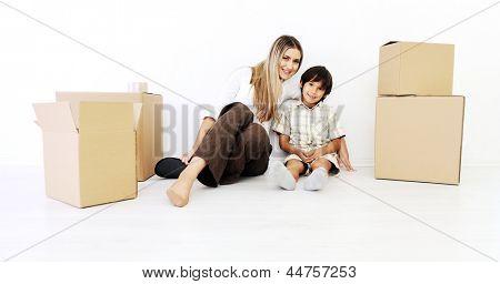 Beautiful smiling woman and little boy sitting alogside cardboard box