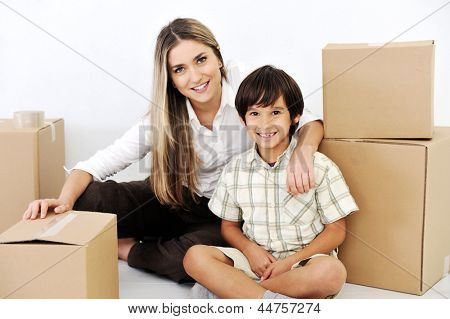 Beautiful smiling woman and little boy openig cardboard box