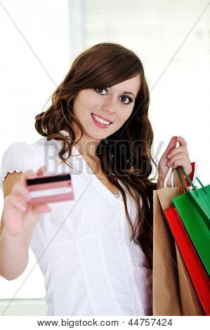 Shopping woman showing business card and smiling