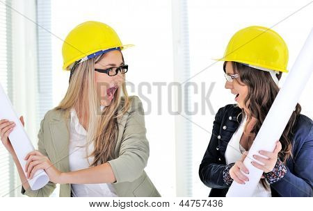 Youngr co-worker getting ready to hit her co-worker with a set of architectural plans