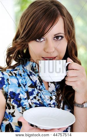 Beautiful woman hold cup of coffee and drinking