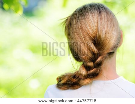 Young blonde girl with braid pigtails in nature