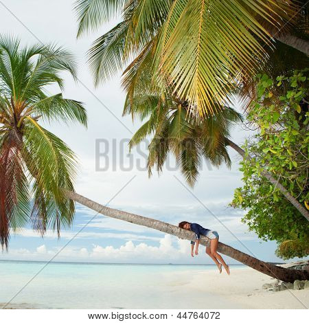 Happy woman lying upon palm tree on the beach