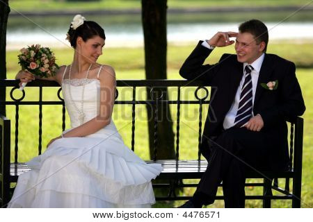 Newlywed Couple Sat On Park Bench