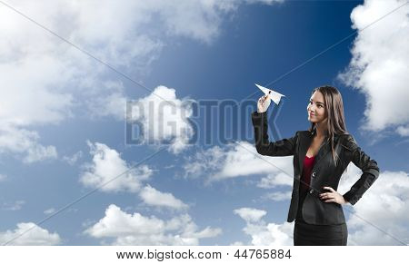 Beautiful business woman throwing a paper plane, against a beautiful blue sky