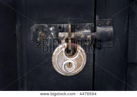 Rusty Antique Padlock On A Black Door