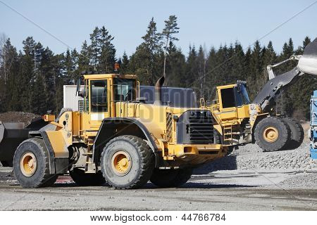 giant trucks, bulldozers working inside industrial site, gravel and sand