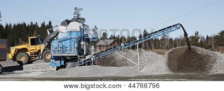 heavy duty trucks loading gravel onto pit