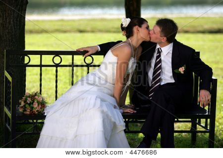Newlywed Couple Kissing On Park Bench