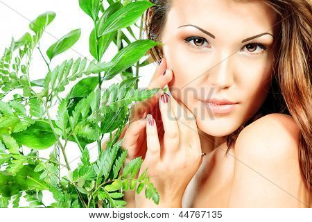 Beautiful young woman with perfect skin standing among fresh green leaves. Isolated over white background
