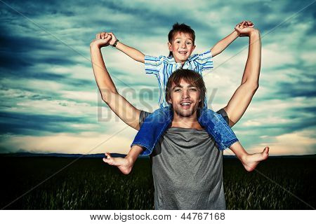 Happy father holding his little son in the wheat field over beautiful cloudy sky.