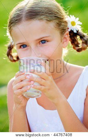 Healthy kid, milk - Portrait of lovely girl drinking fresh milk outdoors