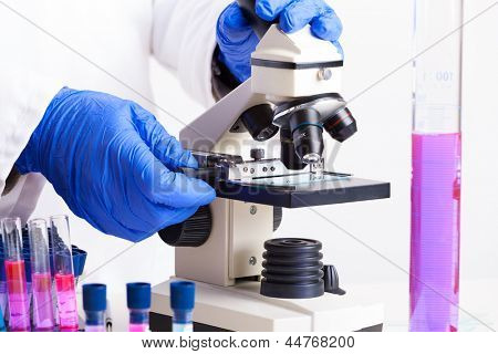 Lab technician working with equipment: tweezers, microscope, test tubes  filled with colored fluid, chemical flasks