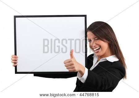 Enthusiastic woman giving the thumb's up and holding a whiteboard
