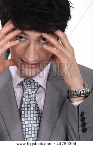 businessman with hands to forehead facing pressure