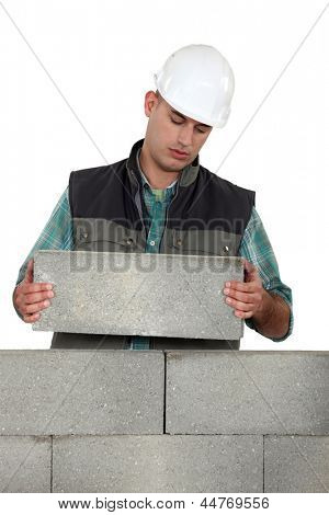 Bored tradesman laying cinder blocks