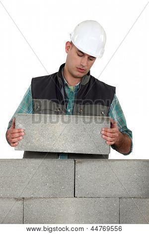 Bored tradesman laying cinder blocks