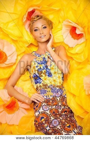 Beautiful young blond woman in colourful dress lying among big yellow flowers