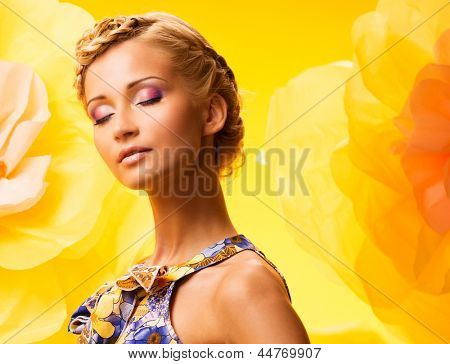 Beautiful young blond woman with closed eyes in colourful dress among big yellow flowers