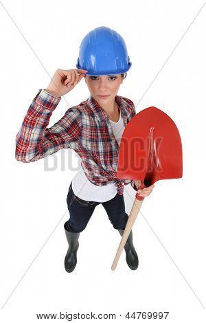Tradeswoman assertiva segurando uma pá