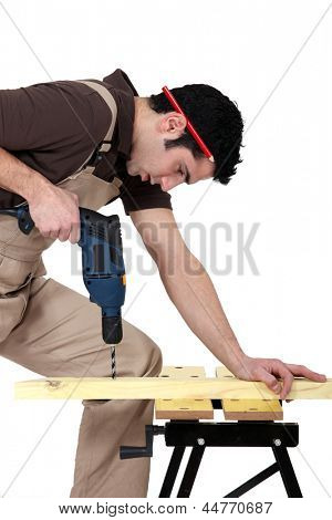 Carpenter drilling a piece of wood