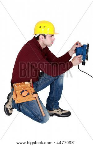 Man kneeling with power sander
