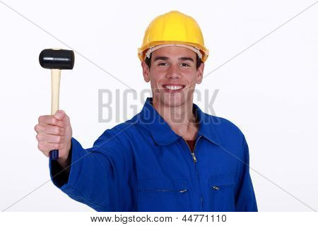 Eager young worker holding rubber mallet