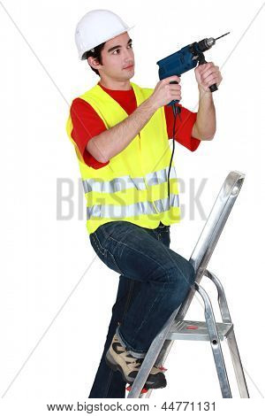 Man holding drill whilst stood on ladder