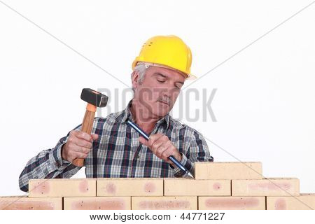 Worker using hammer and chisel on wall