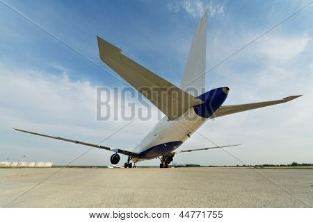 Rear view at airplane standing on parking from low angle