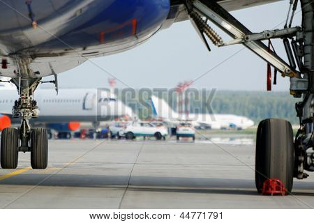 View at airfield from under wing of plane standing on parking