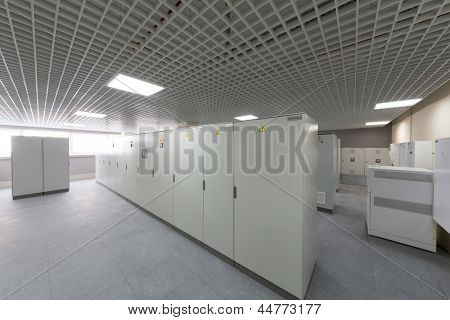 Room with rows of racks with equipment for telecom.