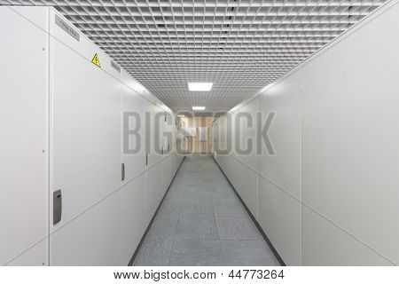 Long aisle with racks of equipment for telecom.