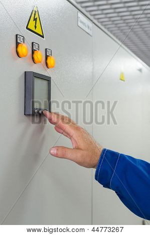 A man presses a button control on equipment for telecom.