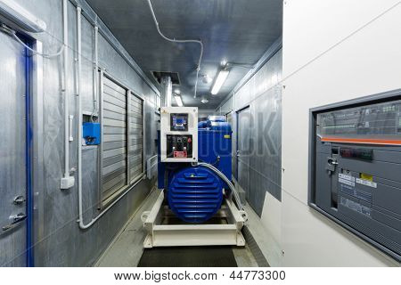 Diesel generator for backup power in room with control panel..