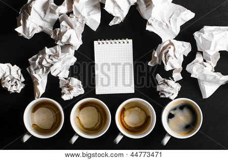 business creativity concept. empty and full cups of fresh espresso with crumple wads on desk