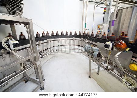 Brown plastic bottles with fresh beer go on conveyor belt at large brewery.