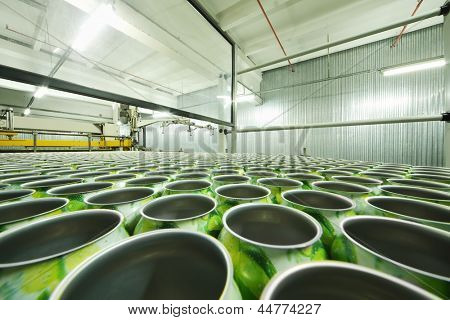 Lot of green aluminum cans for drinks in shop floor at large factory.